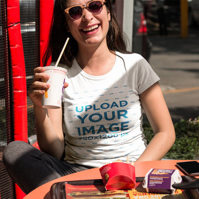 Smiling Customer Drinking a Small Soda While Wearing a Tshirt Mockup Outdoors a16006