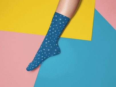 Mockup of an Extended Leg Wearing a Sock While Against a Tricolor Surface a15597