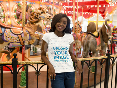 Young Black Girl Wearing a Tshirt Mockup While Happily Standing Against a Carousel a16044