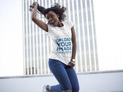 Mockup of a Young Woman Wearing a T-Shirt While Jumping and Smiling Against a Building 16047