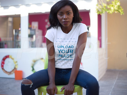 Tshirt Mockup Featuring a Young Black Girl Wearing a Round Neck Tee While Sitting Down Outdoors a16055