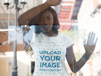 Through the Window Mockup of a Young Black Woman Wearing a Tshirt While Lying on the Window a16053