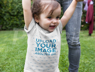 Mockup of a Baby Girl Walking with her Mom in the Park While Wearing a Round Neck Tee a16073
