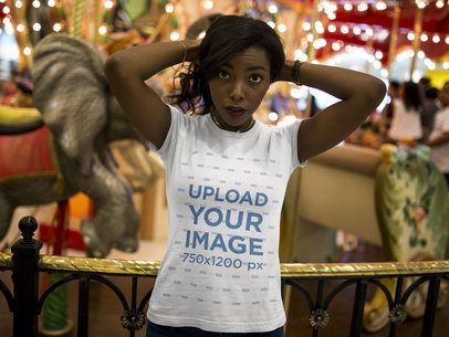Woman Wearing a T-shirt Mockup While Standing Against a Carousel 16045