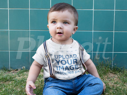 Little Baby Wearing a Round Neck Tee Mockup While Sitting Down in the Grass a16083