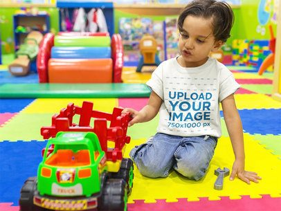 Mockup of a Kid Playing with a Truck While Wearing a T-Shirt Mockup at the Playground a16136
