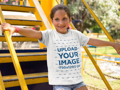 Smiling Kid Going Down Some Yellow Stairs While Wearing a Round Neck T-Shirt Mockup a16166