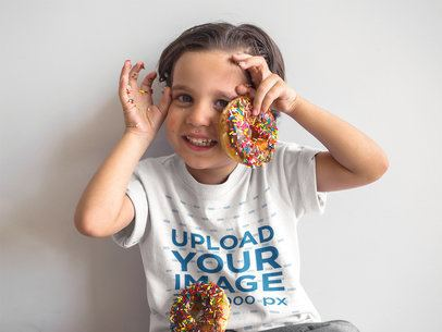 Mockup of a Happy Kid Playing with Donuts While Wearing a Round Neck T-Shirt a16150