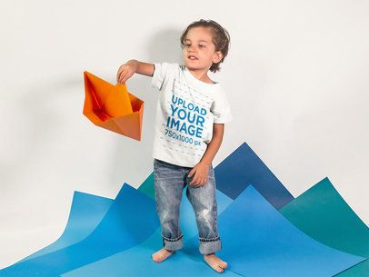 Little Kid Playing with a Paper Boat While Wearing a Round Neck Tshirt Template a16142