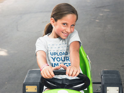 Pretty Girl Wearing a T-Shirt Mockup While on a Green Plastic Go Kart a16158