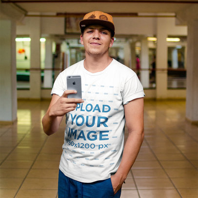 Selfie Mockup of a Young Guy Wearing a T-Shirt and a Hat While Facing a Mirror a16221