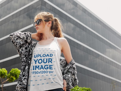 Pretty Girl Wearing a Bella Canvas Tank Top Mockup While Walking Near a Big Building a16120