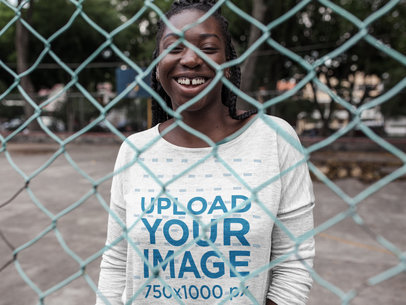 Smiling Black Girl with Dreadlocks Wearing a Long Sleeve Heather T-Shirt Mockup While Near a Fence Outdoors a16208