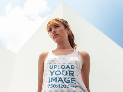 Mockup of a Beautiful White Girl Wearing a Bella Flowie Tank Top While Near a White Building a16117