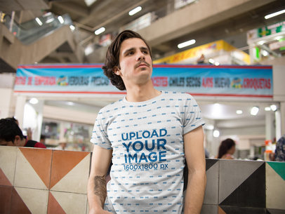 Mockup of a Young Guy with Moustache and a Tattoo Weairng a Sublimated Tee While inside a Urban Market a15356