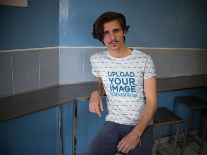 Hipster Dude Wearing a Sublimated Tee Mockup While Waiting for his Food Against a Blue Wall a15373