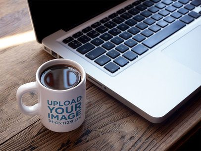 Cup of Coffee Mockup Near a MacBook a16461