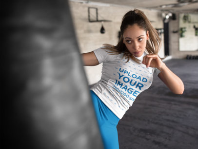 Mockup of a Woman Kicking a Heavy Bag in a Boxfit Class Wearing Custom Sportswear a16844