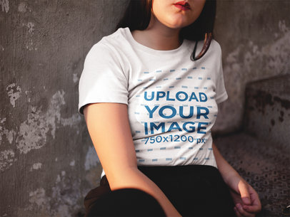 Woman Sitting Down Against a Concrete Wall While Wearing a T-Shirt Mockup a16962