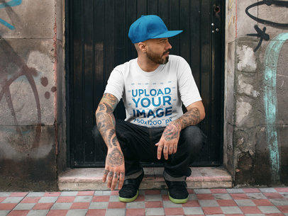 Mockup of a Tattooed Man Looking Aside While Wearing a T-Shirt Mockup and a Hat a16984