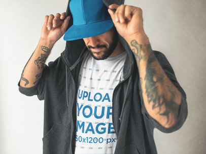 Middle Aged Tattooed Man with a Hat Wearing a Round Neck Tee Mockup and a Hoodie a17023