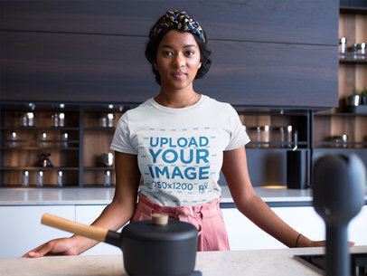 Woman Wearing a Round Neck Tshirt Mockup While in her Kitchen Counter a17128