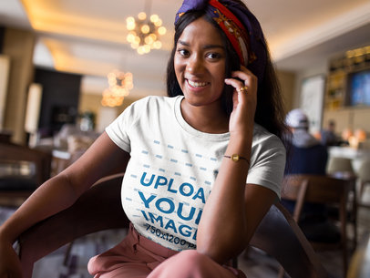 Smiling Beautiful Woman Wearing a T-Shirt Mockup While Inside a Hotel Lobby a17129