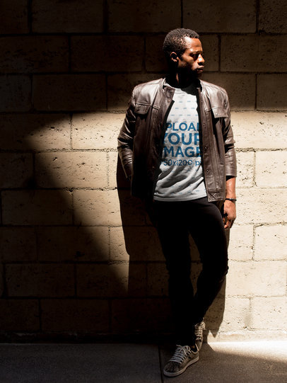 Tshirt Mockup of a Man Wearing a Tee and a Leather Jacket Against a Wall a17160