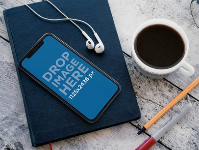 iPhone X Mockup Lying on top of a Book While Near a Coffee Cup and Headphones a17220