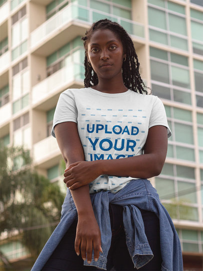 Mockup of a Black Girl Wearing a Round Neck Tee Template While Standing Near a Tall Building a17322