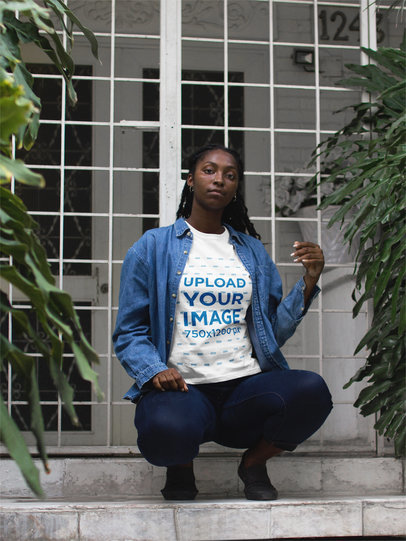 Black Girl Wearing a Tshirt Mockup While Crouching in a Building Entrance a17323