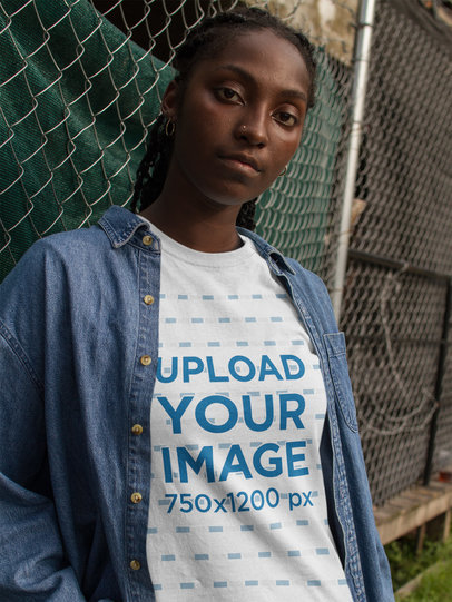 Urban Portrait of a Black Girl Wearing a Round Neck Tee Mockup and a Denim Jacket Against a Fence a17319