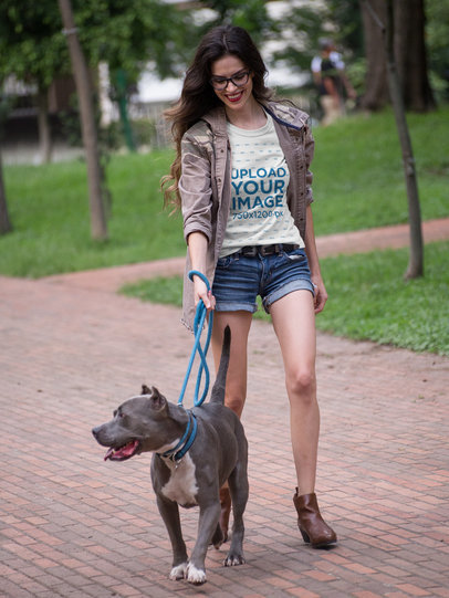 Pretty Woman Walking the Dog Wearing a T-Shirt Mockup at the Park a17354