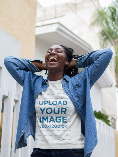 Smiling Black Girl Wearing a T-Shirt Mockup and a Denim Jacket While Walking in the Street a17317