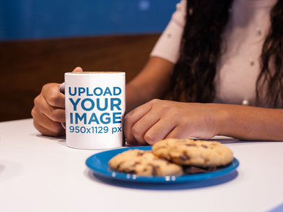 Girl Holding a Coffee Mug Mockup While Near Cookies a17336