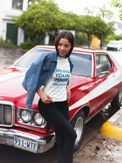 beautiful girl wearing a round neck tee mockup while lying against a muscle  car a17464