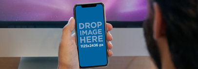 Man Holding an iPhone X Mockup Against a TV a17616