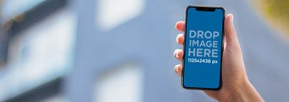 Man Holding an iPhone X Mockup Against a Blurry Building a17681