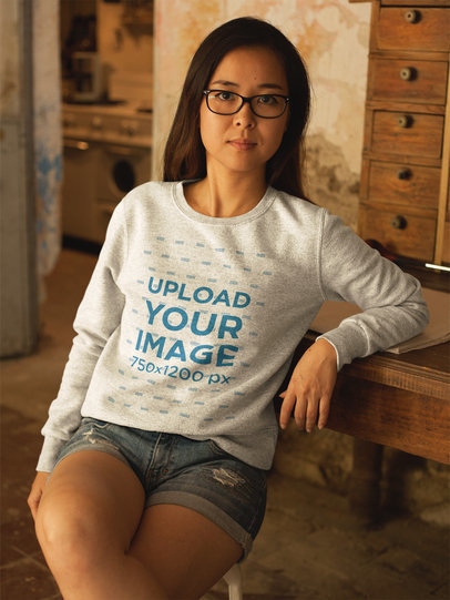 Asian Girl Wearing a Crew Neck Sweatshirt Mockup While Lying Against a Vintage Desk a17605
