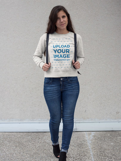 Pretty Girl with Backpack Wearing a Crewneck Sweatshirt Template While Standing Against a White Wall a17630