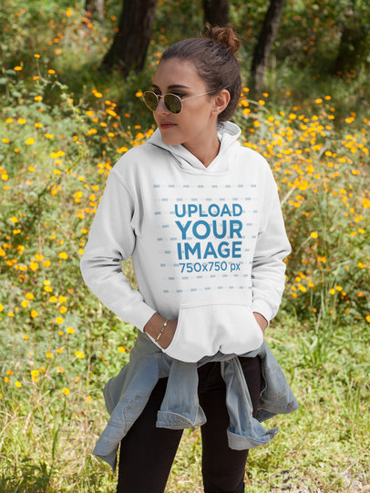 Girl Wearing a Hoodie Mockup While Standing Near Flowers Outdoors a17673