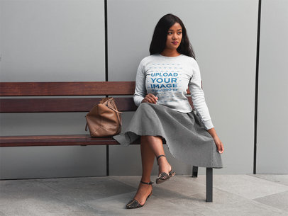 Pretty Girl Wearing a Crew Neck Sweatshirt Template While Sitting on a Bench a17753
