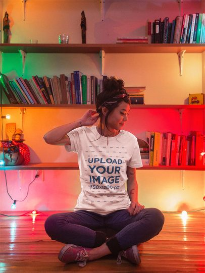 Girl Sitting Next to Christmas Lights and Bookshelves Wearing a Round Neck T-Shirt Mockup a17780