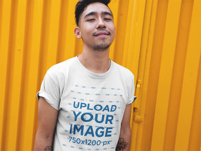 Asian Dude Wearing a Round Neck Tshirt Mockup While Standing Against a Yellow Wall a17804