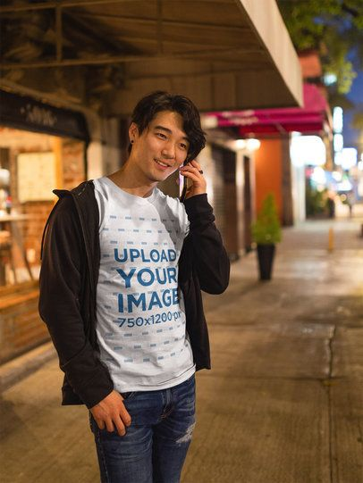 Happy Asian Man Talking on the Phone Wearing a T-Shirt Mockup a17809