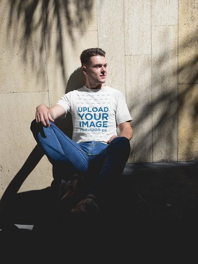 Man Wearing a Tshirt Template While Sitting Against a Wall a17858