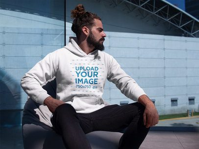 Man Wearing a Pullover Hoodie Mockup Near a Building a17764