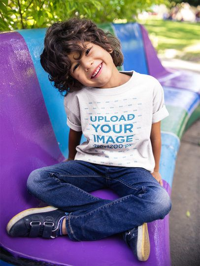 Boy Sitting on a Bench Wearing a Tshirt Template While Smiling a17864