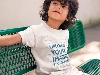 Boy Wearing a Tee Mockup Sitting on a Green Bench a17873