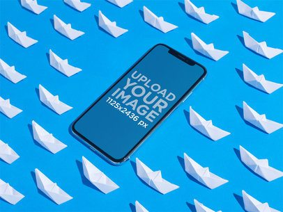 iPhone X Mockup on a Blue Surface Surrounded by Paper Boats a19118